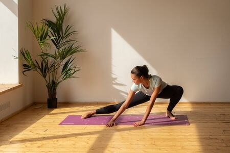 young woman doing stretching exercise at home Stock fotó