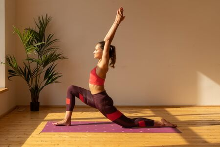 young woman doing yoga exercise on yoga mat at home near window