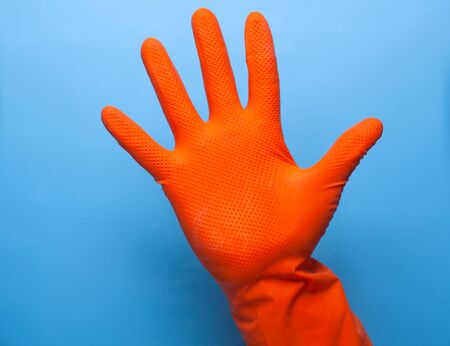 hand in orange glove showing stop gesture isolated on blue background