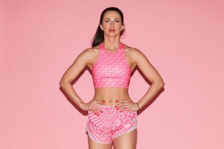 sporty woman posing isolated on pink background
