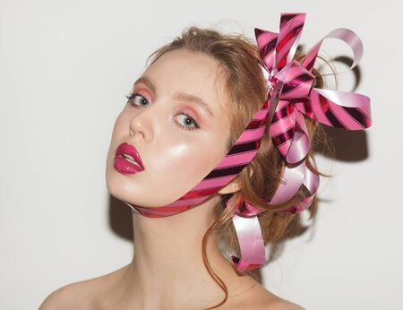 beauty young woman with gift ribbon on head, studio close up portrait