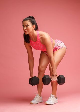 sportswoman in doing deadlift exercise with dumbbells isolated on pink background