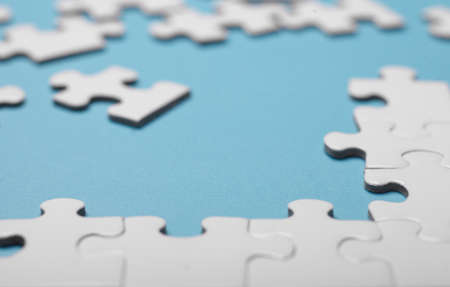 white blank puzzle isolated on blue background, selective focus