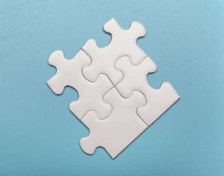 four connected white blank puzzle parts isolated on blue background