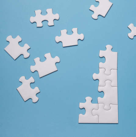 white blank puzzle isolated on blue background, top view