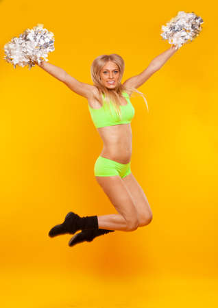 smiling cheerleader girl jumping with cheerleading pompoms isolated on yellow background