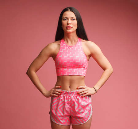 athletic woman in pink sportswear isolated on pink background