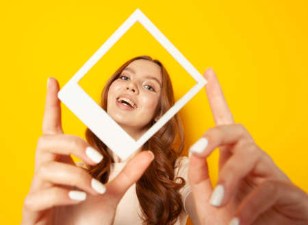 young smiling woman holding in hands photo frame with her face isolated on yellow background, selfie concept