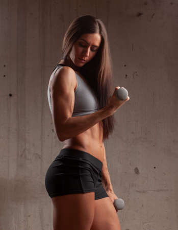 young beautiful brunette muscular woman doing biceps exercise with dumbbell near stone wall
