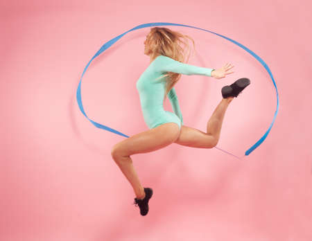 young sporty woman with gymnastic ribbon jumping on pink background