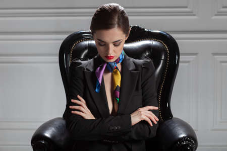 fashion caucasian business woman in black suit sitting in chair