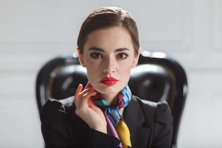 fashion caucasian model in black business suit sitting in chair