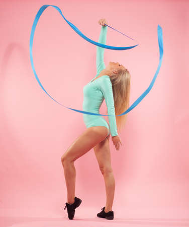 young sporty woman with gymnastic ribbon on pink background