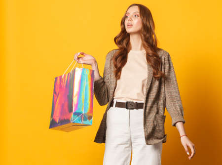 stylish woman with shoping bag isolated on yellow background, looking left