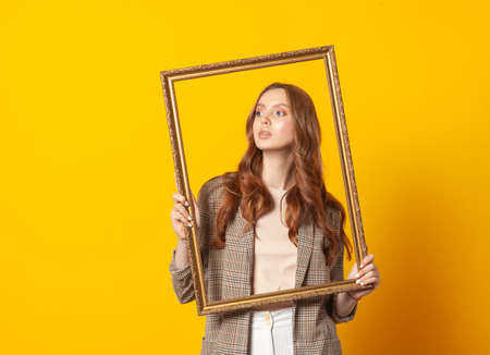 portrait of woman with empty picture art frame isolated on yellow background 版權商用圖片