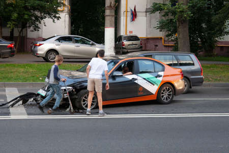 MOSCOW, RUSSIA - SEPTEMBER 6, 2020: children looking on auto car accident victim in BMW carsharing 新聞圖片