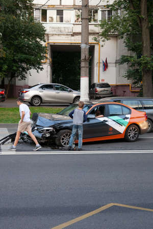 MOSCOW, RUSSIA - SEPTEMBER 6, 2020: children pry on auto car accident victim in BMW car-sharing