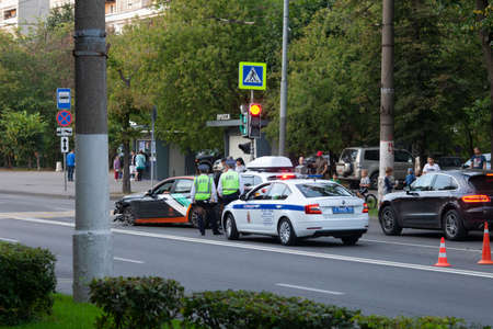 MOSCOW, RUSSIA - SEPTEMBER 6, 2020: Russian policemen near crashed BMW carsharing, crosswalk car accident 新聞圖片