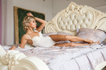 Beautiful sexy blonde girl posing in the morning in the hotels interior