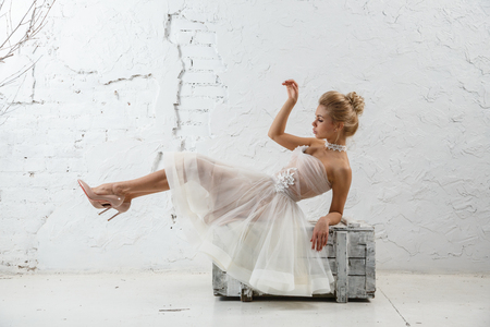 Beautiful sexy blonde woman in white dress posing against white wall Stock Photo