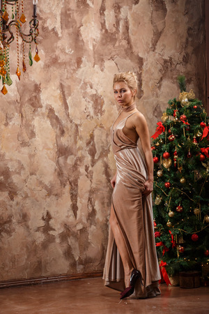 Beautiful sexy blonde in dress posing in a castle by the Christmas tree and piano Stock Photo