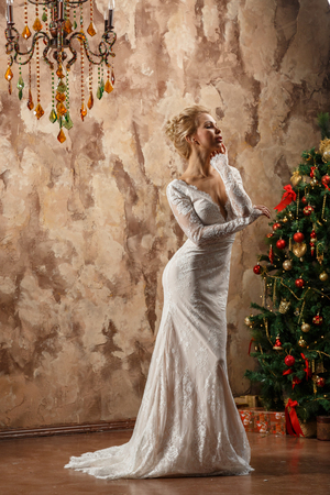 Beautiful sexy blonde girl in white wedding dress posing in a castle near the wall and a Christmas tree Stock Photo