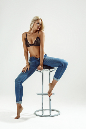 Beautiful sexy blonde in underwear and jeans sitting on a chair and posing, on a white background Stock Photo