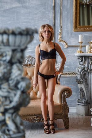 Bella ragazza bionda sexy che propone al mattino negli alberghi interni