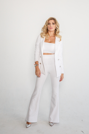 Beautiful sexy blonde in a white suit (pants, jacket) posing on white background