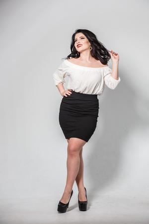 Beautiful brunette girl in skirt and blouse posing on white background