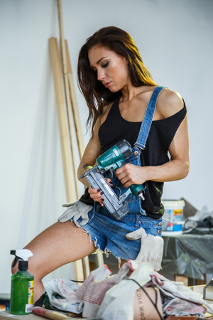 Beautiful girl sexy fitness makes repairs in a bright white room