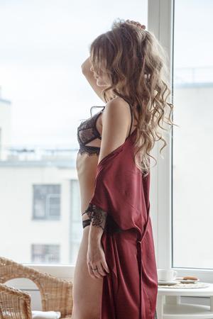 Beautiful brunette girl in underwear posing by the window in the morning