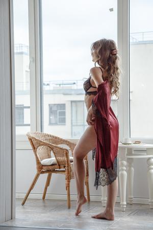 朝の窓でポーズのセクシーな下着で美しいブルネットの少女