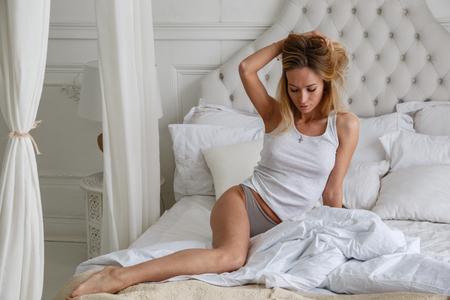 朝、ベッド、部屋、インテリア、寝室のベッドでポーズ美しい少女のセクシーなブロンド 写真素材