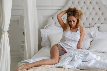 Beautiful girl sexy blonde posing on the bed in the morning, bed, room, interior, bedroom
