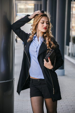 go shopping: Beautiful sexy blonde business walking and posing on the Sunny city Stock Photo