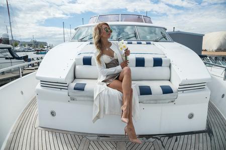 Beautiful sexy blonde girl posing on yacht, ship, boat
