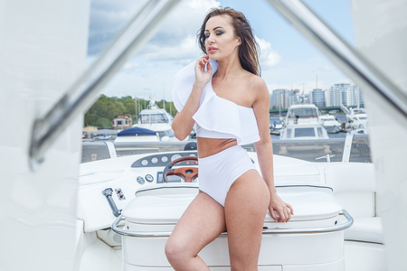 1 person: Beautiful blond woman in swimsuit posing at the port near the yacht, on the yacht