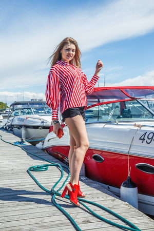 Beatiful blonde woman in denim shorts and white blouse posing near yacht in seaport