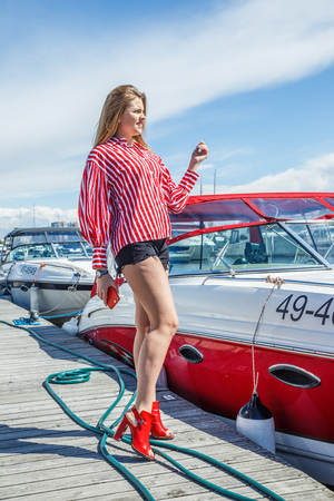 1 person: Beatiful blonde woman in denim shorts and white blouse posing near yacht in seaport