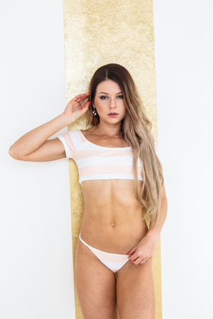Beautiful blonde girl in underwear, bathing suit paziuret in the interior of the hotel Stock Photo