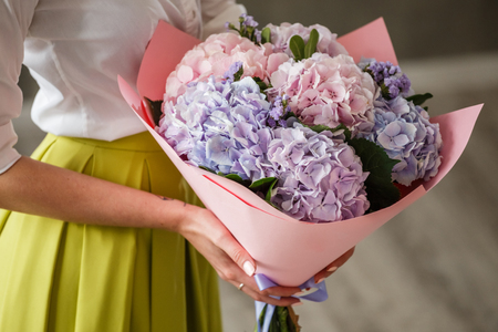 provocative woman: Beautiful blonde girl posing in a bright interior with a bouquet of flowers Stock Photo