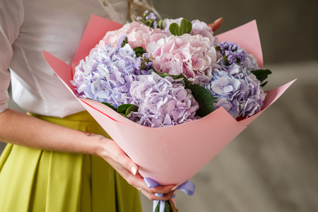 female sexuality: Beautiful blonde girl posing in a bright interior with a bouquet of flowers Stock Photo
