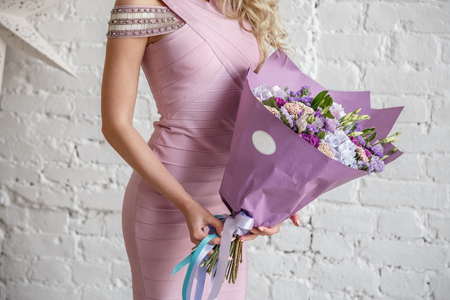 Beautiful blonde girl posing in a bright interior with a bouquet of flowers Stock Photo - 84736271