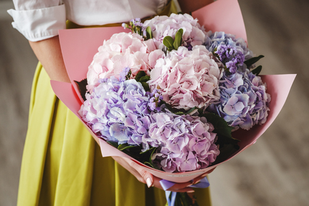 Beautiful blonde girl posing in a bright interior with a bouquet of flowers Stock Photo