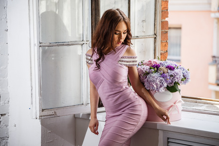 Beautiful girl brunette in pink dress posing with flowers in the interior of the window