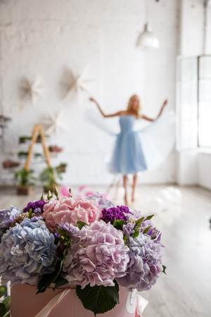 female sexuality: Beautiful girl blonde in dress posing with flowers in bright interior