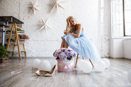 Beautiful girl blonde in dress posing with flowers in bright interior