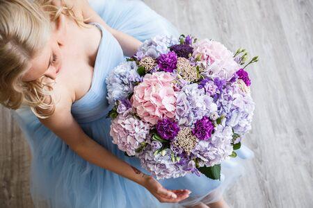 sexualidad: Hermosa chica rubia en vestido posando con flores en el interior brillante