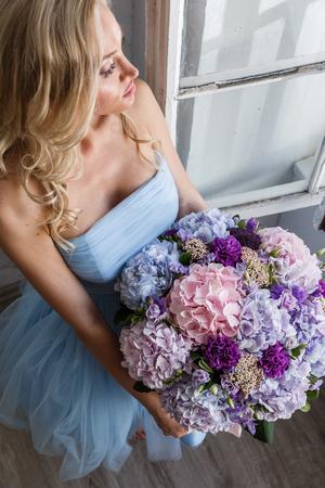 Mooie meid blonde in jurk poseren met bloemen in helder interieur